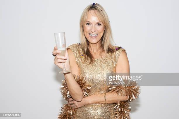senior woman wearing golden dress, celebtraing new year's eve - gold dress stock pictures, royalty-free photos & images