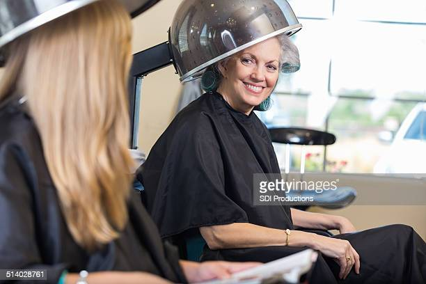 Senior woman wearing hair rollers during beaty salon appointment