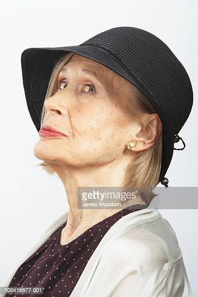 Senior woman wearing hat, rolling eyes to the side, side view,
