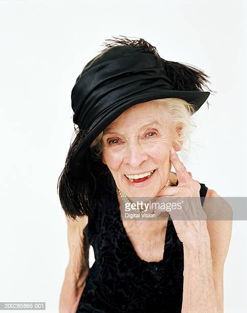 Senior woman wearing hat, touching face with hand, smiling, portrait