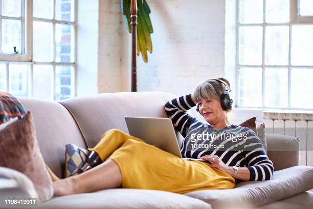 senior woman wearing headphones watching movie on laptop - using laptop stock pictures, royalty-free photos & images
