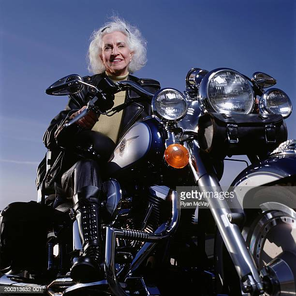 Senior woman wearing leathers sitting on motorcycle, posing in studio, portrait, low angle view