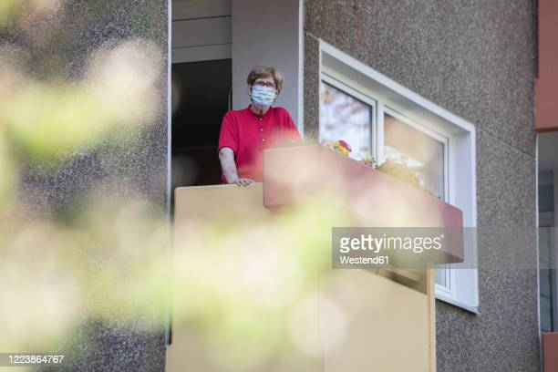 senior woman wearing mask on balcony, retirement home - lockdown stock-fotos und bilder