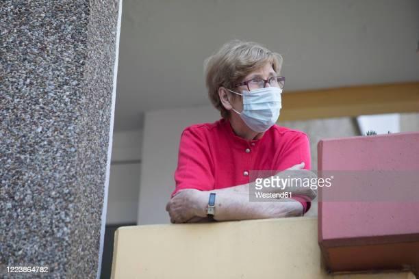 senior woman wearing mask on balcony, retirement home - munskydd ensam bildbanksfoton och bilder