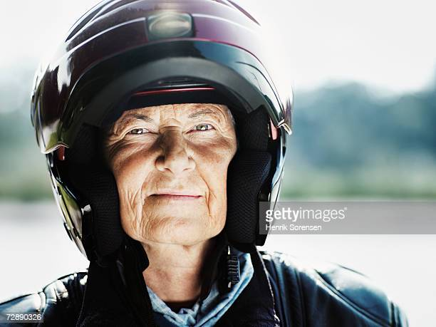 senior woman wearing motorcycle helmet, portrait - crash helmet stock pictures, royalty-free photos & images