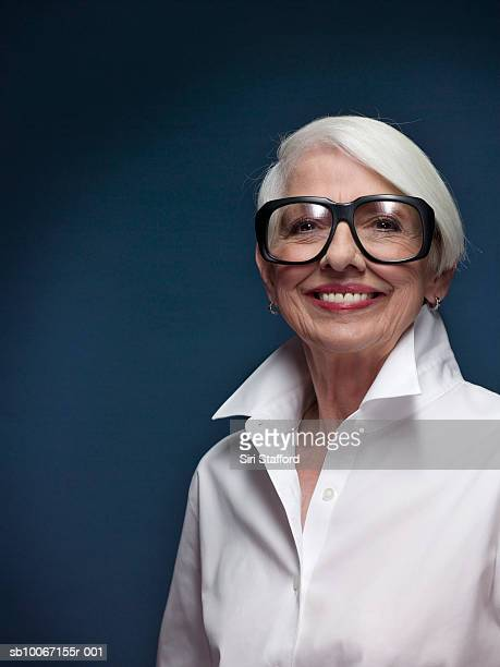 senior woman wearing oversized glasses standing in studio, portrait - big bobs stock photos and pictures