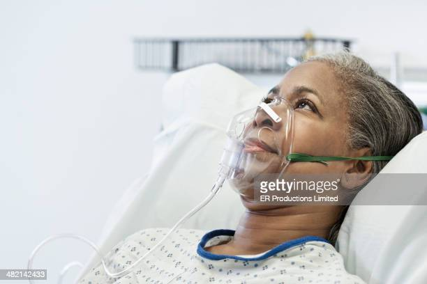 senior woman wearing oxygen mask in hospital bed - breathing device stock pictures, royalty-free photos & images