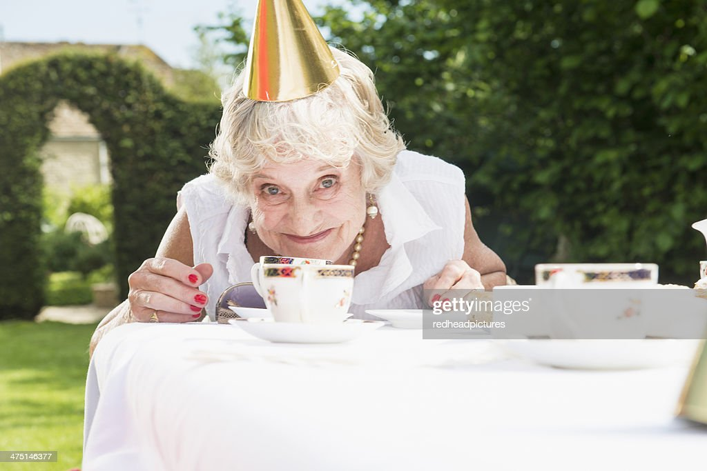 Senior woman wearing party hat looking at camera, smiling : Stock Photo