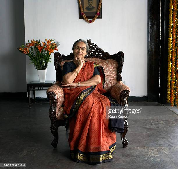 senior woman wearing sari sitting in armchair smiling, portrait - sari stock pictures, royalty-free photos & images