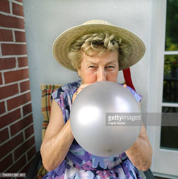 senior woman wearing straw hat, blowing balloon - inflating stock pictures, royalty-free photos & images