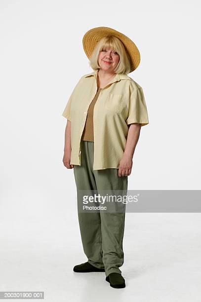 Senior woman wearing straw hat posing in studio, portrait