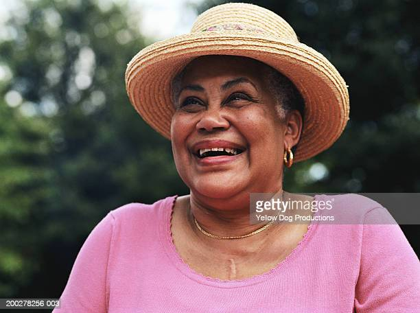 senior woman wearing straw hat, smiling - black hat stock pictures, royalty-free photos & images