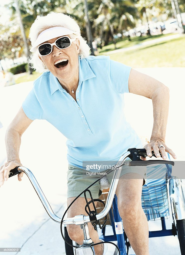 Senior Woman Wearing Sunglasses and a Sun Visor Riding a Bicycle : Stock Photo