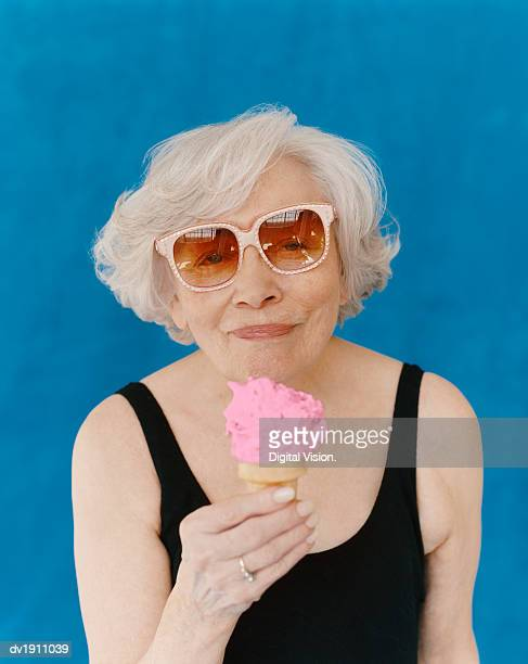Senior Woman Wearing Sunglasses and a Swimming Costume Eating an Ice Cream