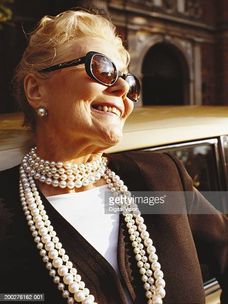 senior woman wearing sunglasses and pearl necklace, smiling, close-up - pearl jewellery stock pictures, royalty-free photos & images