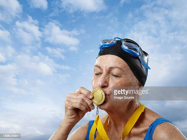 Senior woman wearing swimming cap kissing gold medal