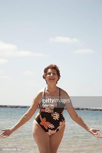 Senior woman wearing swimming costume on beach, smiling, portrait