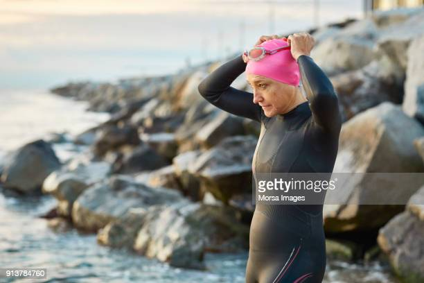 senior woman wearing swimming goggles at beach - hobbies stock pictures, royalty-free photos & images
