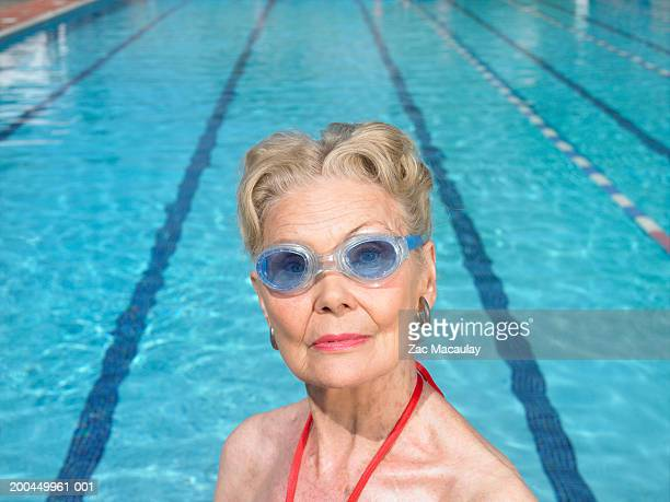 Senior woman wearing swimming goggles standing by pool, portrait