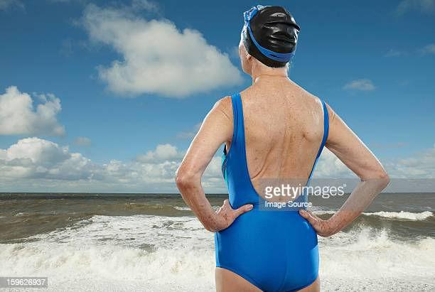 senior woman wearing swimsuit looking towards sea - old woman in swimsuit stock pictures, royalty-free photos & images