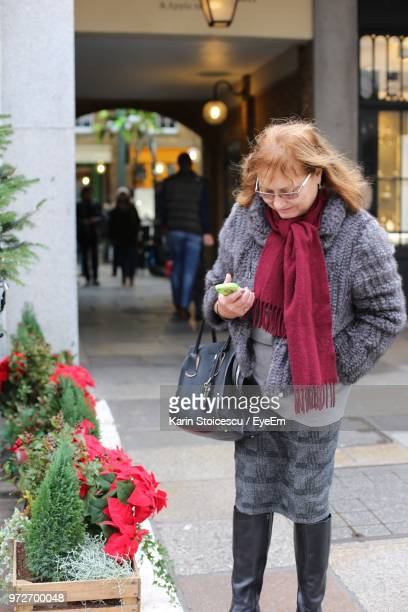 Senior Woman Wearing Warm Clothing While Standing By Flowering Plants On Footpath In City