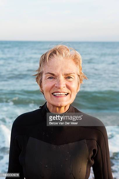Senior woman wearing wetsuit in front of the sea.