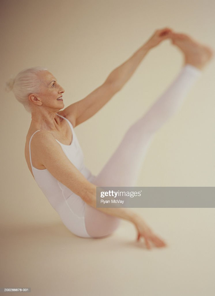 Senior woman wearing white leotard performing gymnastics on floor : Stock Photo