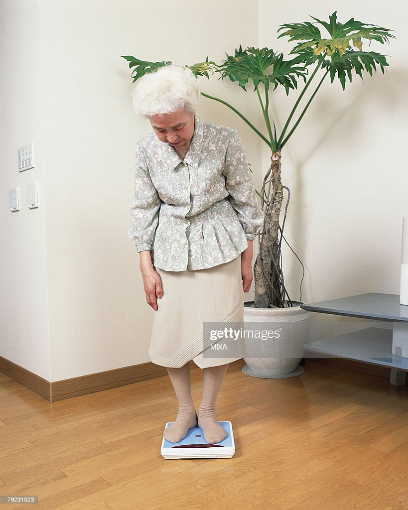 A senior woman weighing in a living room : Stock Photo