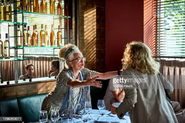 senior woman welcoming friend in restaurant - arms outstretched stock pictures, royalty-free photos & images