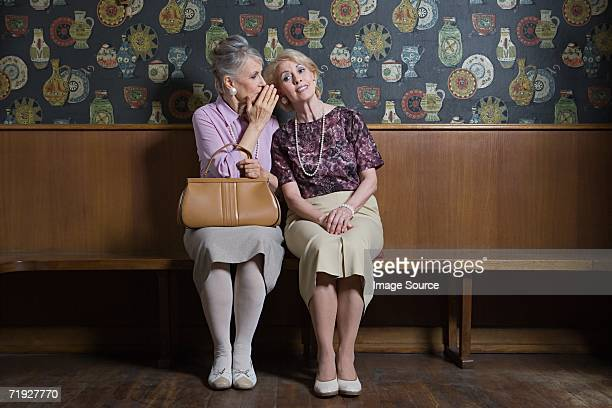 senior woman whispering to friend - whispering stock pictures, royalty-free photos & images