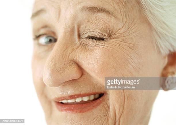 senior woman winking, close-up. - solo una donna anziana foto e immagini stock
