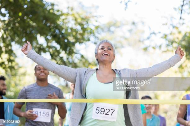 senior woman wins a charity race - finish line stock pictures, royalty-free photos & images