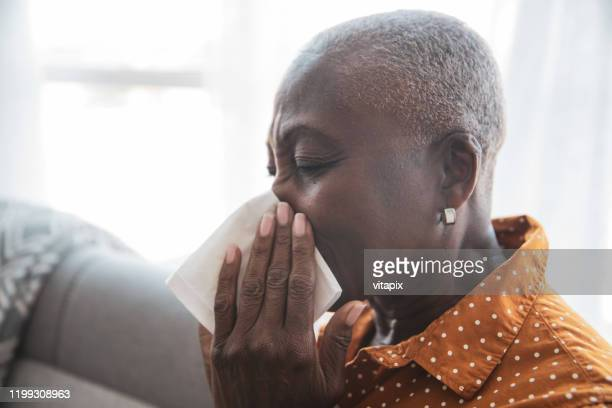 senior woman with a cold - blowing nose stock pictures, royalty-free photos & images