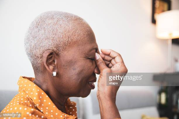 senior woman with a headache - sinus stock pictures, royalty-free photos & images