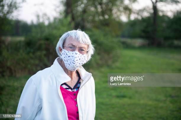 senior woman with a home made face mask - bril brillen en lenzen stockfoto's en -beelden