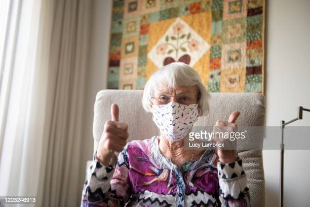 senior woman with a home made face mask showing thumbs up - covid-19 stock pictures, royalty-free photos & images