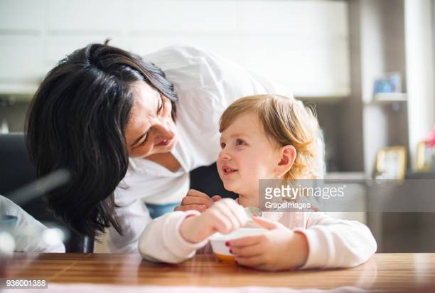 Senior woman with a small girl in the kitchen at home.