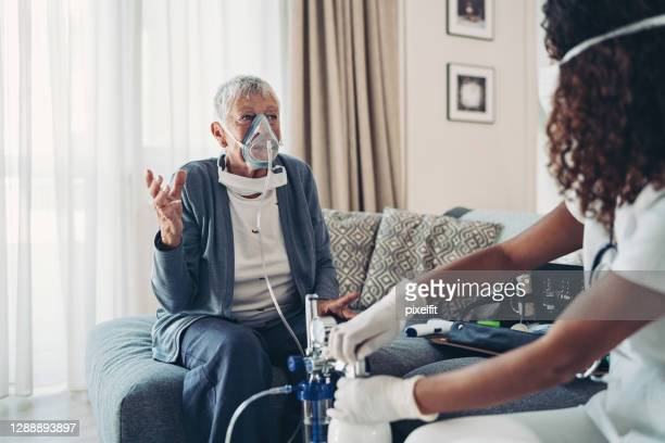 senior woman with an oxygen mask talking to a doctor - oxygen mask stock pictures, royalty-free photos & images