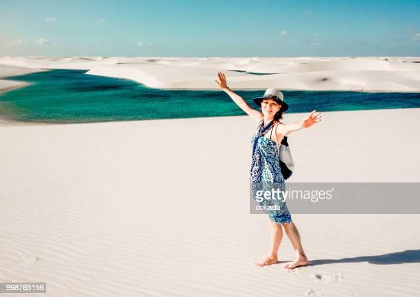 senior woman with arms open at lençois maranhenses - lencois maranhenses national park stock pictures, royalty-free photos & images