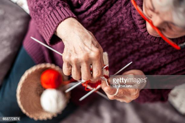 senior woman with arthritic hands doing crochet - arthritis stock pictures, royalty-free photos & images
