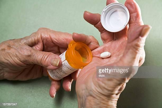 senior woman with arthritis holding prescription medicine pill bottle
