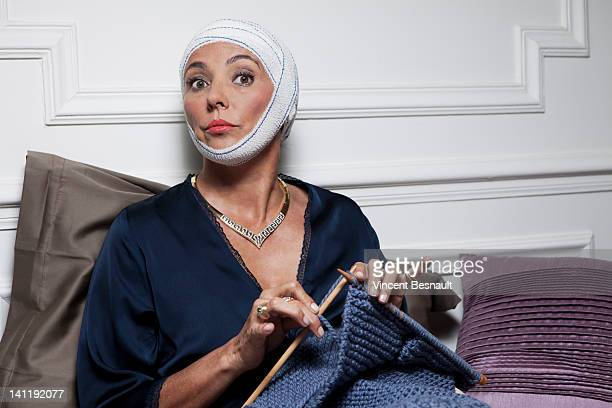 Senior woman with bandages on head knitting