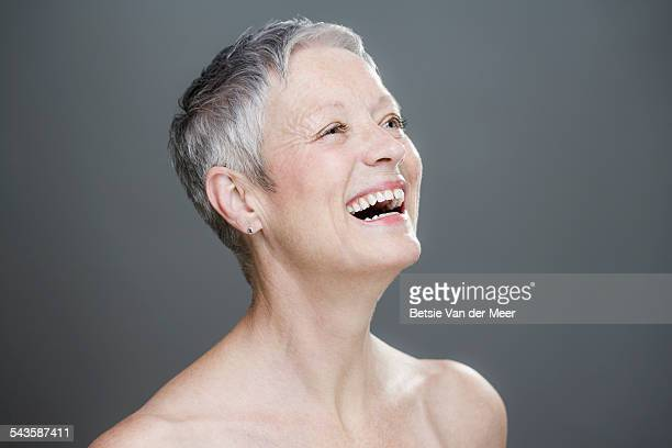 Senior woman with bare shoulders, laughing.