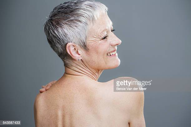 Senior woman with bare shoulders smiling.