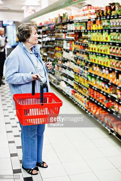 Senior Frau mit Korb Schecks Supermarkt-Regal