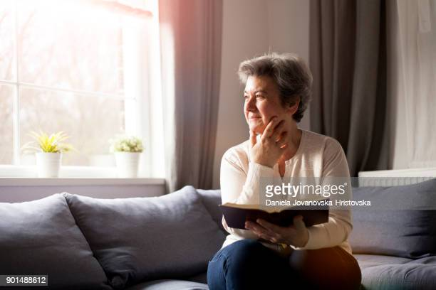 senior woman with bible - bible stock pictures, royalty-free photos & images