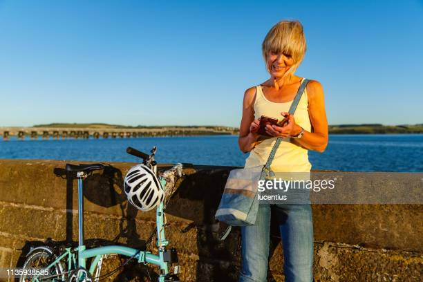senior woman with bike and phone. - foldable stock pictures, royalty-free photos & images