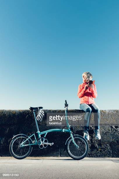senior woman with bike and phone. - dundee scotland stock pictures, royalty-free photos & images