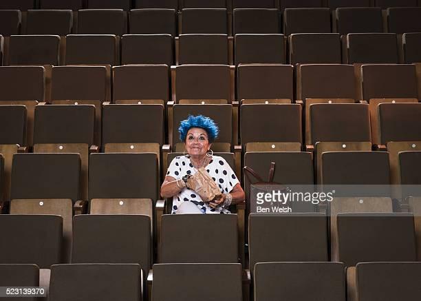 Senior woman with blue hair enjoying a movie.