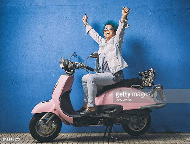 Senior woman with blue hair on a motor bike.